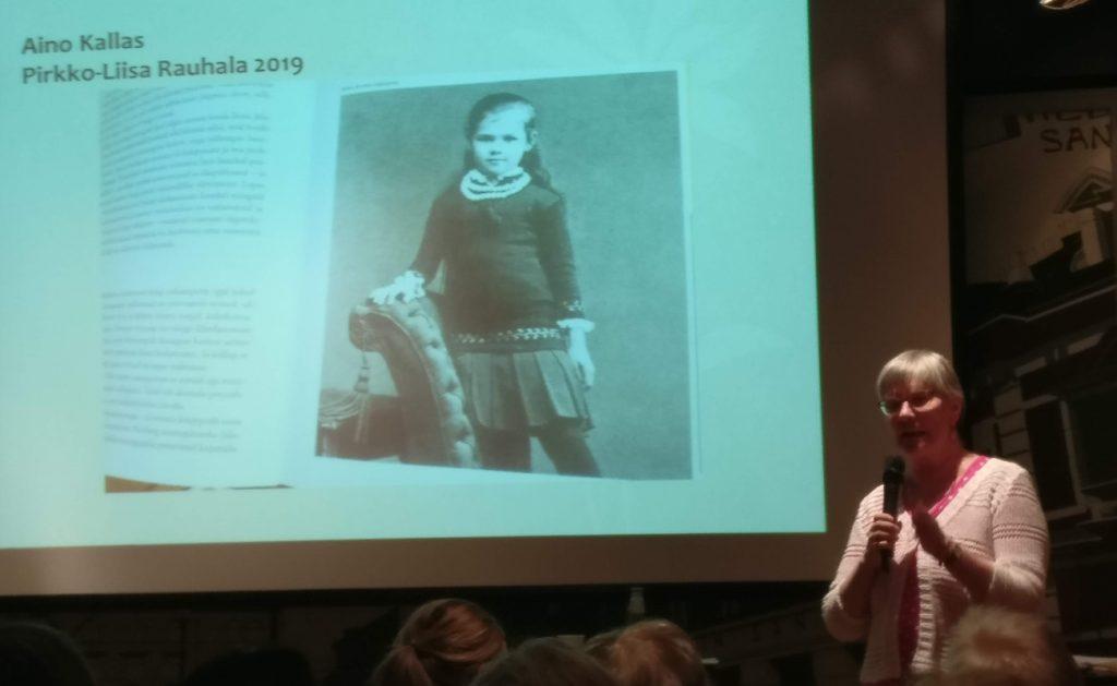 Pirkko-Liisa Rauhala Päivälehden museossa kertomassa Aino Kallaksen miehistä. Diakuvassa Aino Kallas lapsena.
